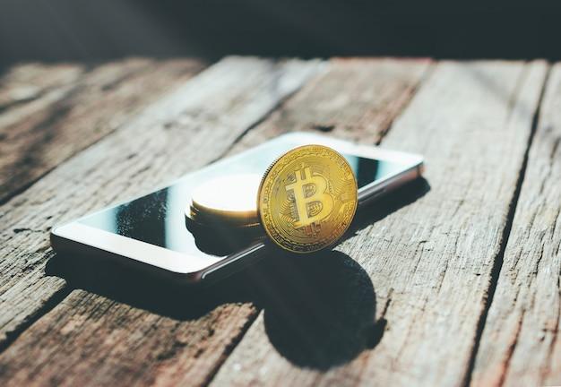 Золотая монета биткойн на криптовалюте мобильного телефона