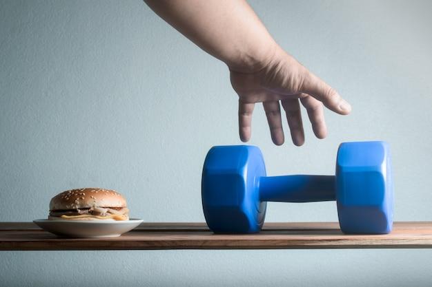 男性の手がダンベルのアイデアを拾うために達する減量の食事療法の概念。
