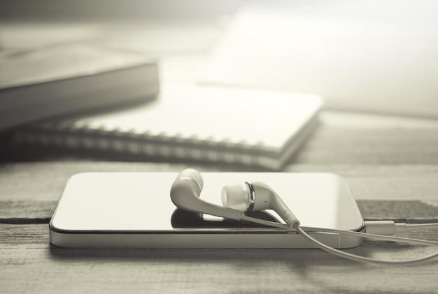 ぼやけている教育机の背景を持つ木製のテーブルの上のレトロなスマートフォン。