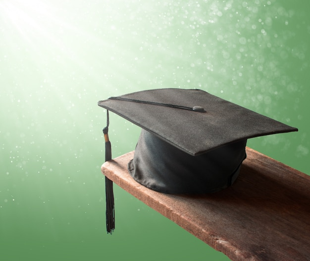 卒業の帽子、抽象化された緑の背景卒業概念と木の帽子