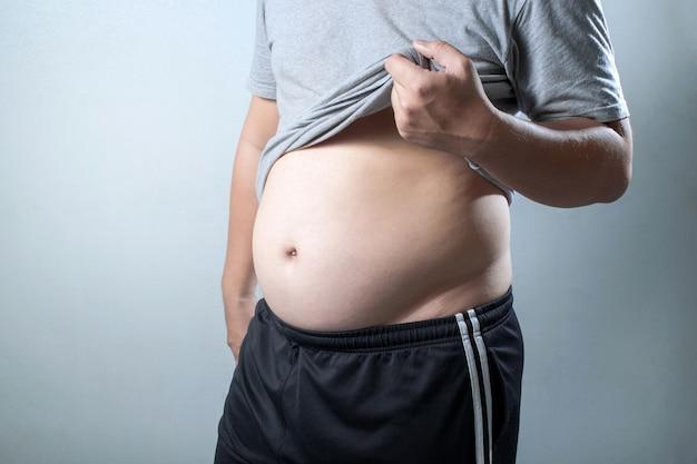 アジアの太った男の肖像画は、彼の体と大きな腹を見せてくれる。