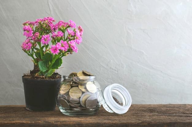 木製のテーブルの上のガラスの瓶に黄金のコイン