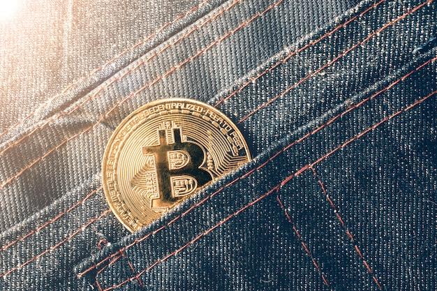 Золотая монета биткойн в кармане джинсов.