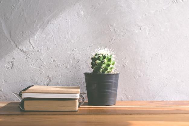 木製のテーブルモダンなインテリアの背景概念に関するノートブックとサボテンの花。