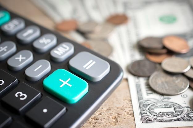 木板の経済成長の概念にお金で電卓と緑色のボタンのクローズアップ。