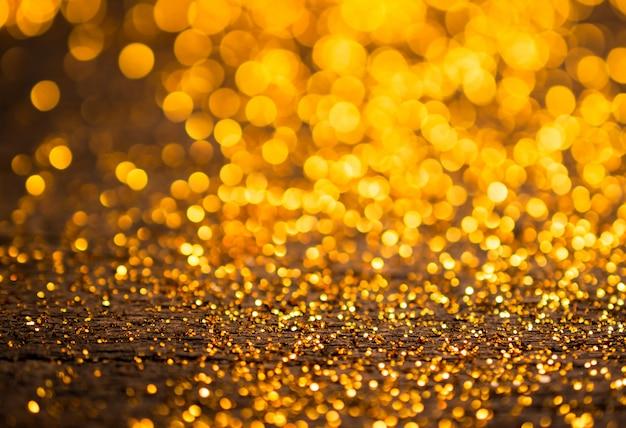 キラキラヴィンテージライトの背景。ダークゴールドとブラック。デフォーカス