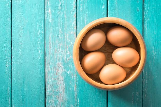 オーシャンブルーのテーブルの上に木製のボウルに卵を上から表示します。