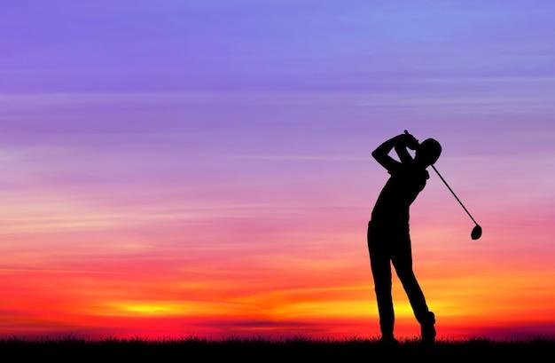 美しい夕日の間にゴルフをするシルエットのゴルファー