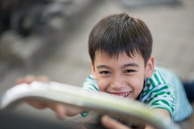 Крупный план маленький милый мальчик играет слайдер на детской площадке