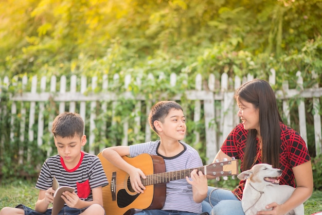 シングルママと息子が公園で楽しんで一緒にギターを弾く