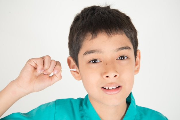 小さな男の子は彼の耳をきれいにカットン芽を使用します