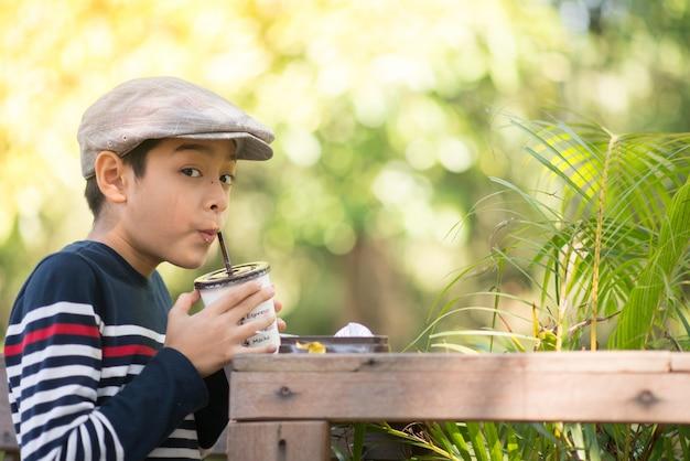 Маленький мальчик пьет шоколадное молоко в зеленом кафе