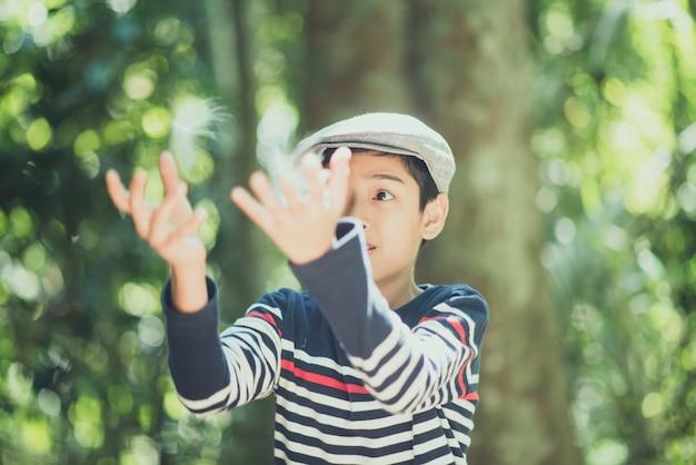 少年が庭の空気に浮かぶ花を吹く