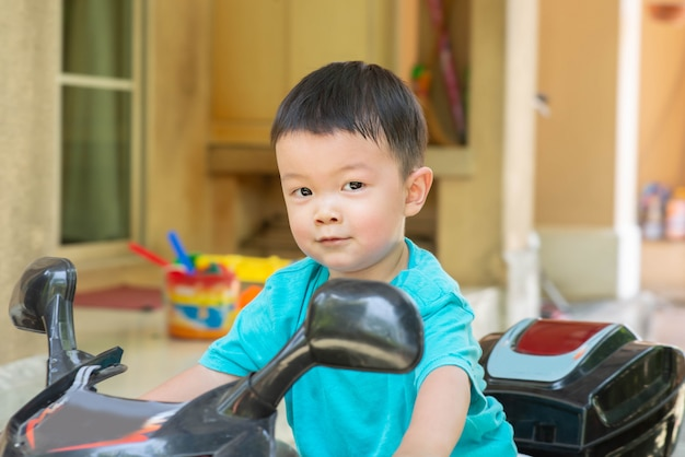 幸せな顔で家の中で自転車のおもちゃに乗って小さなアジアの少年