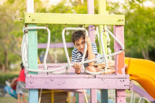 屋外の遊び場で遊ぶ少年