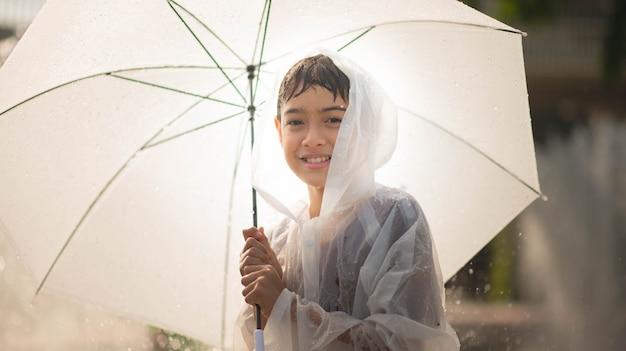 水と遊ぶ少年は布と傘の下の噴水を削除します