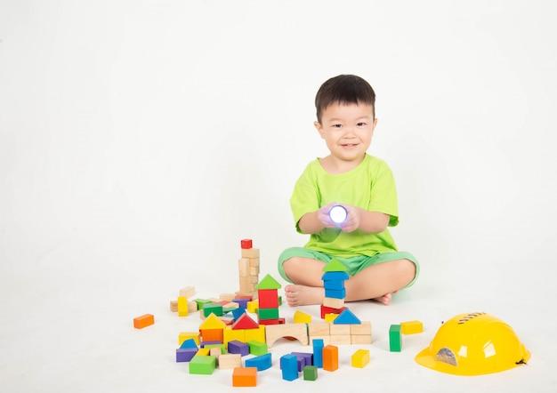 ウッドブロックを再生する小さなアジアの幼児少年ヘルメットエンジニアを着用