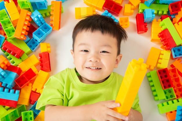 幸せでカラフルなプラスチックブロックを遊んでいる小さな男の子幼児