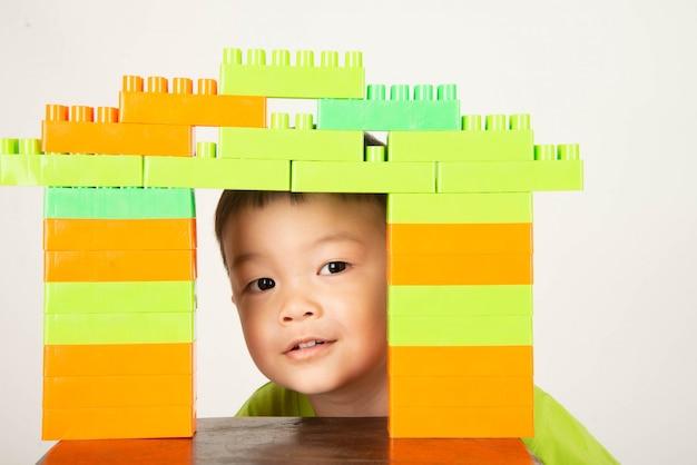 幸せでカラフルなプラスチック製のレンガブロックを遊んでいる小さな少年幼児