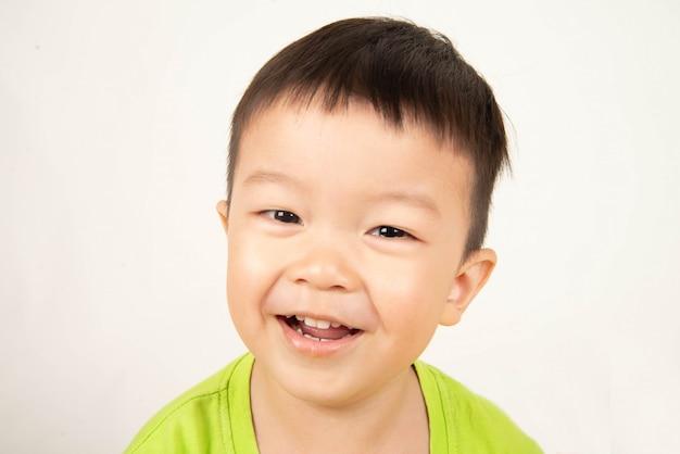 アジアの幼児少年の笑顔で幸せそうな顔を閉じる