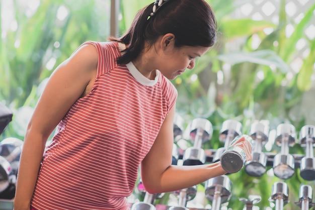 Азиатская женщина разрабатывает упражнения в потере веса тренажерный зал