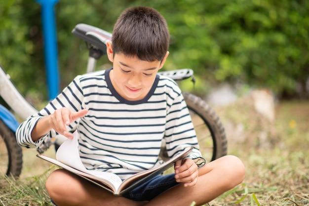 公園で自転車に座って本を読んで小さな男の子