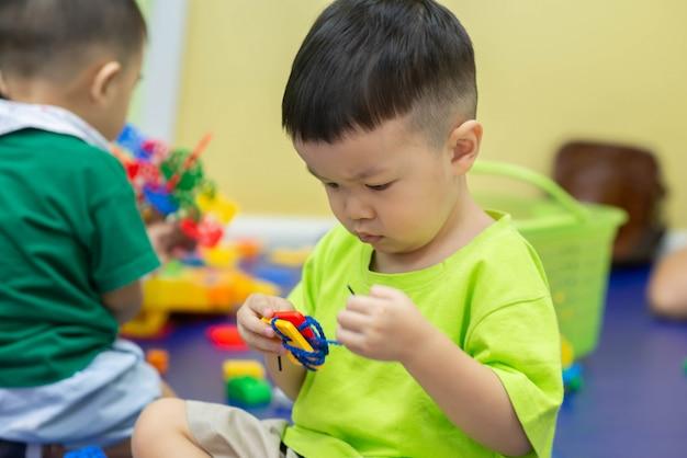 部屋で一緒におもちゃを遊ぶ男の子