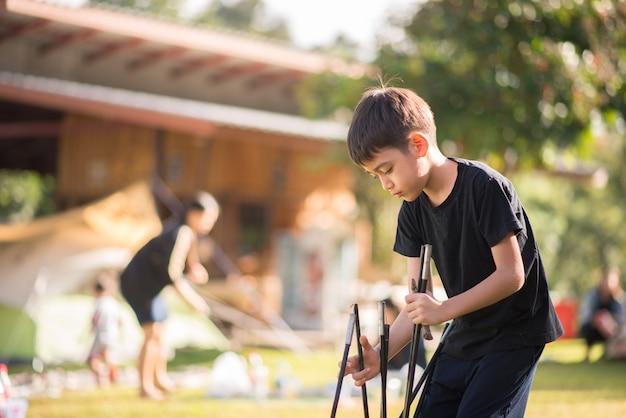 家族の休日の夏の時間とキャンプのためのテントを構築する小さな男の子