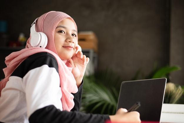 Мусульманская женщина держит ручку в руке, надевает беспроводные наушники на голову, смотрит снаружи, думает о проекте, делает работу дома, затуманила ноутбук на деревянном столе,