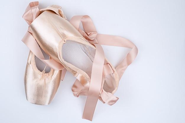 白い背景の上に置くピンクのサテンバレエシューズ
