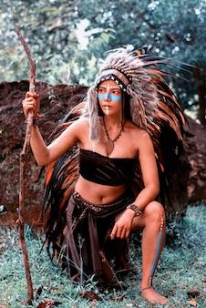 Красивая женщина носить головной убор из перьев птиц.