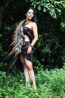 Абстрактное художественное оформление фона красивой женщины положило головной убор из перьев птиц на ее плечо