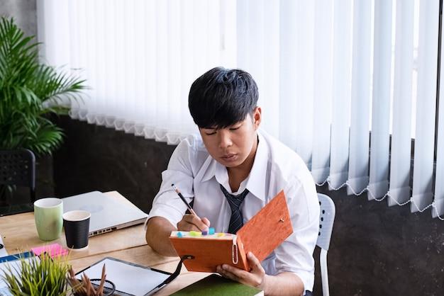 ハードカバーの本にメモを書いて、仕事、オフィスの時間、ハードワークと忙しい、深刻な感情の実業家