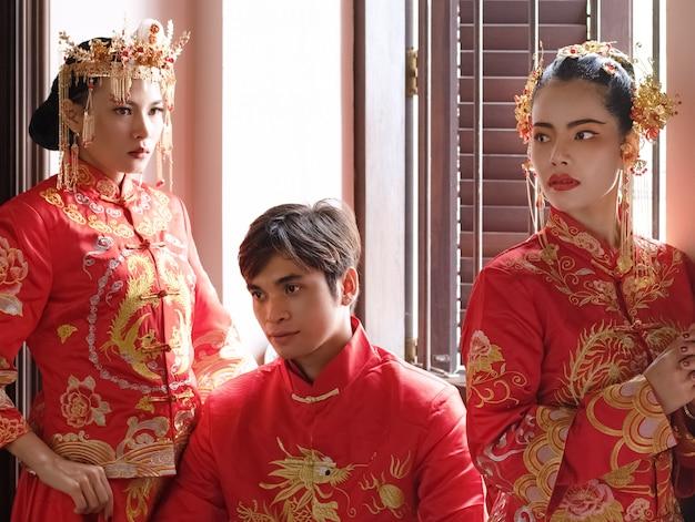 Красивый портрет трех моделей в красном костюме позирует у окна