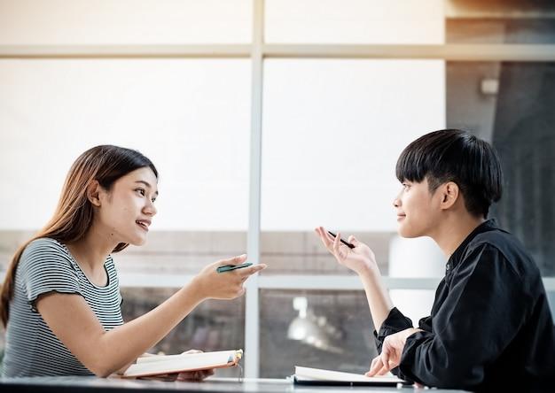 Двое молодых подростков говорят о проекте, делают работу вместе, в конференц-зале, размыто вокруг света.
