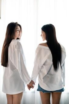 Женщины держатся за руки и смотрят друг на друга со сладкими эмоциями
