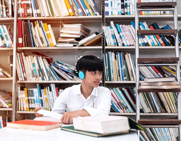 図書館で本のデータを読んだり検索したりする彼女の頭にヘッドフォンを身に着けている若いティーンエイジャー