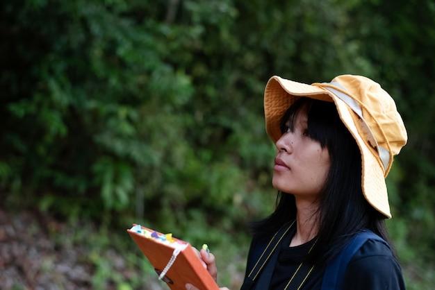 Юная леди в желтой шапке, пишущая на книге, исследующая на пути