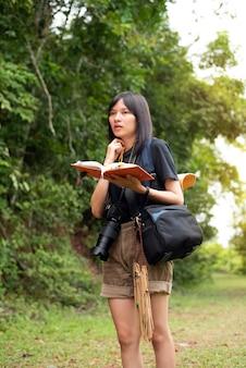 Молодой подросток рюкзак и держа в руке книгу, гуляя в парке