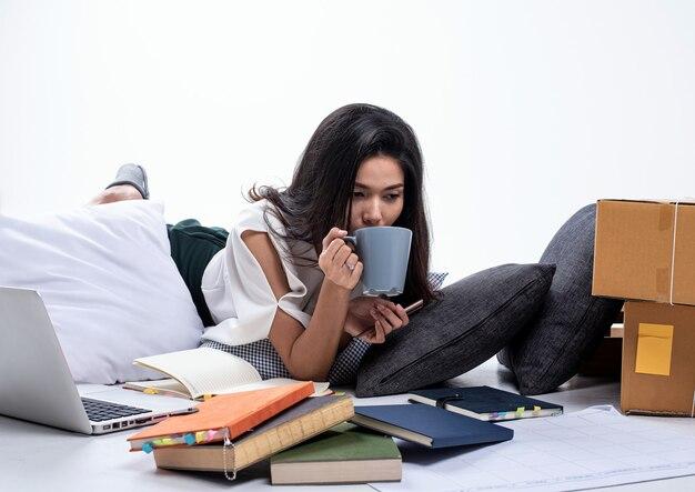 Красивая дама лежит рядом с ноутбуком и почтовым ящиком, пьет кофе во время работы, занимается продажей в интернете, электронной коммерцией, работой дома