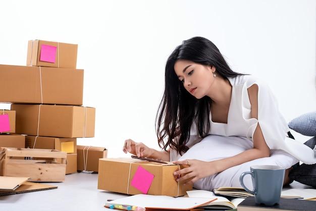 若い美しい女性の梱包とポストボックスの書き込み、オンライン販売、自宅から仕事、幸せな気持ちで