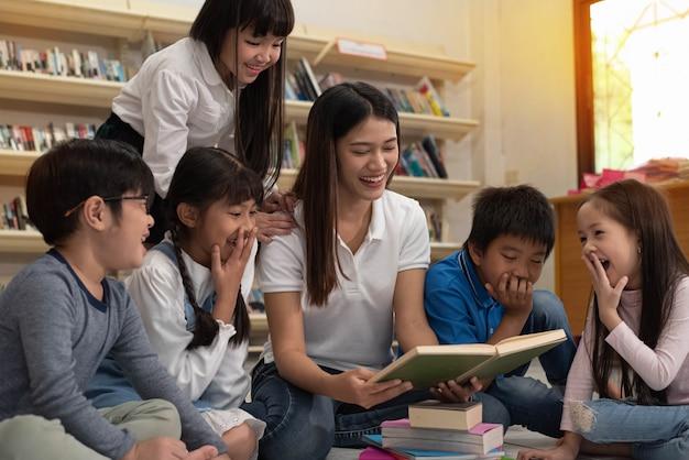 Красивая дама читает книгу с маленькими детьми со счастливым чувством, размытым светом вокруг
