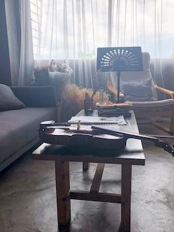 スタジオミュージックルーム。ノート・シートと本の横に机の上に置かれたヴァイオリン、横に置かれたノート・スタンド