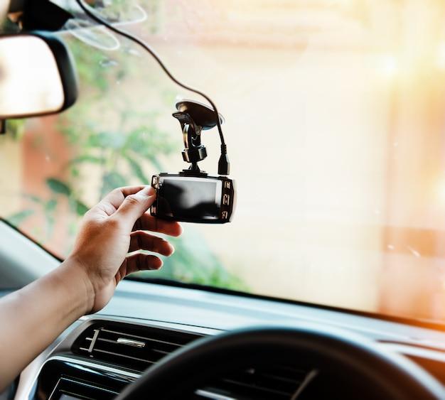 人間の手の選択的な焦点で車のカメラに触れる、運転する前に