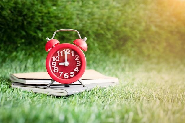 赤い目覚まし時計と本は、緑の草地の床に置かれ、暖かい光のトーン