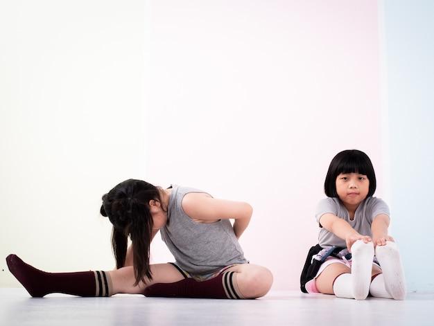 二人の姉妹は体を一緒に伸ばし、運動の前に