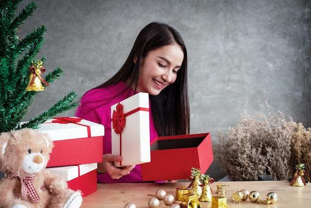 Красавица открыла подарочную коробку, заглянув внутрь с улыбкой и счастливым лицом