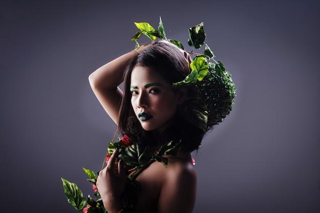 美しさの女性はジャングルのようにポーズをとって、緑の葉と花で体を包んだ