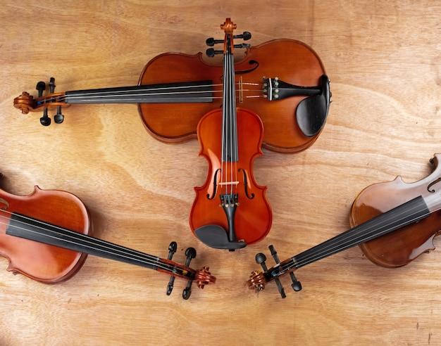 小さいサイズのバイオリンは大きいサイズのバイオリンを、木の板の上に置く