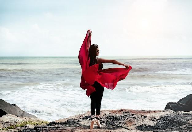 赤いスーツとサテンのバレエシューズを着ている美しさの女性の抽象芸術デザインの背景